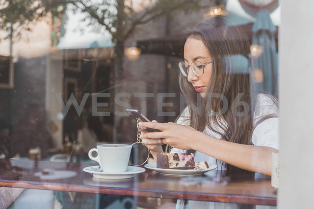 Woman with cake checking her cell phone in a cafe - AFVF00003