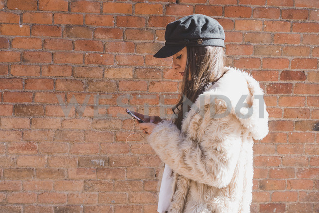 Stylish young woman in front of brick wall using cell phone - AFVF00009