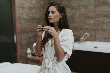 Young woman in a spa enjoying cup of tea - OCAF00132