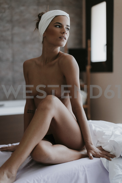 Nude young woman sitting on lounger in a spa - OCAF00138