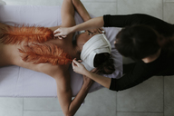 Young woman receiving a massage with feathers in a spa - OCAF00147