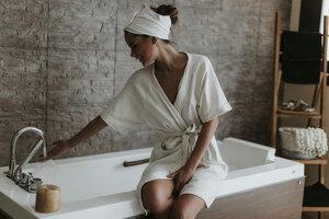 Young woman preparing a bath in a spa - OCAF00150