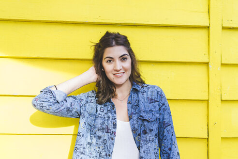 Portrait of smiling young woman in front of yellow wooden wall - AFVF00025