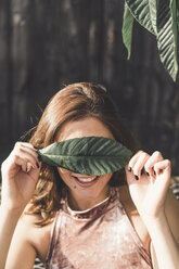 Smiling young woman covering eyes with a leaf - AFVF00034