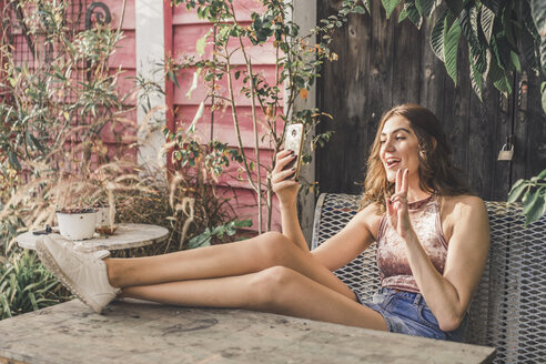 Happy young woman sitting on bench outdoors taking selfie with cell phone - AFVF00040