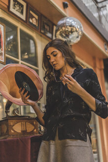 Portrait of pensive young woman standing in front of antique shop holding gramophone record - AFVF00052