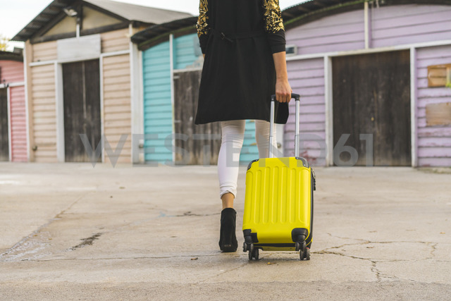Back view of walking woman with yellow trolley bag, partial view - AFVF00058