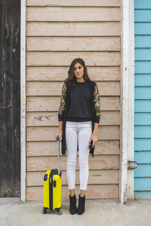 Young woman with yellow trolley bag waiting in front of wooden facade - AFVF00061