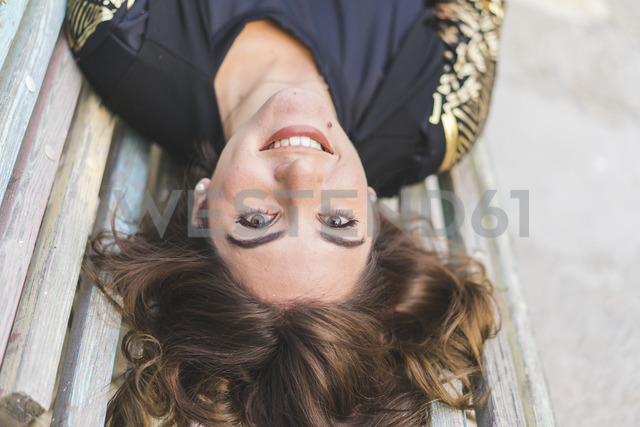 Portrait of laughing young woman lying on a bench - AFVF00064