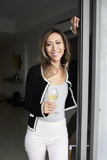 Portrait of smiling woman having a glass of wine at home - IGGF00405