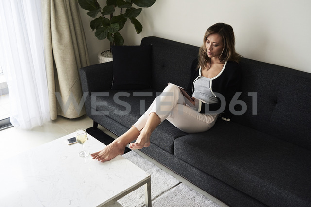Woman at home relaxing on sofa with tablet and glass of wine - IGGF00408