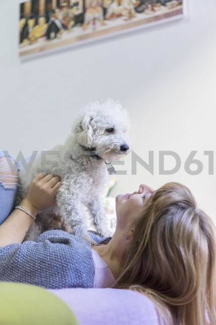 Young woman lying on bed playing with her dog - AFVF00071