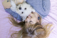 Happy woman lying on bed with her dog - AFVF00074