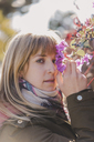 Portrait of woman smelling flowers outdoors - AFVF00083