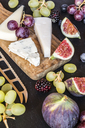Plate with cheese, figs, grapes, blueberries, brambles, pecan, chopping board, knife - SARF03586