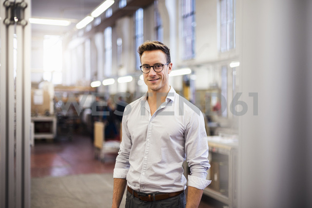Portrait of smiling young businessman in factory - DIGF03334