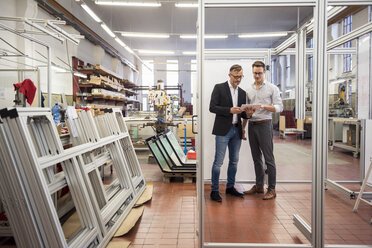 Two businessmen in factory looking at tablet - DIGF03337