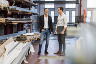 Two businessmen standing in factory storeroom - DIGF03340