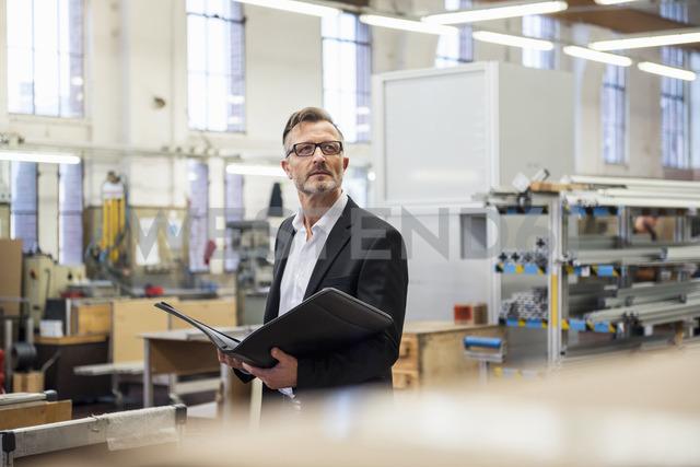 Mature businessman in factory holding folder - DIGF03343