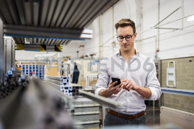 Young businessman using cell phone in factory - DIGF03346