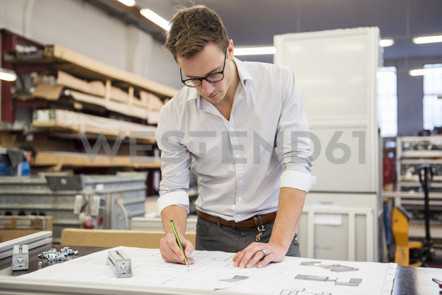 Young businessman in factory working on plan - DIGF03355