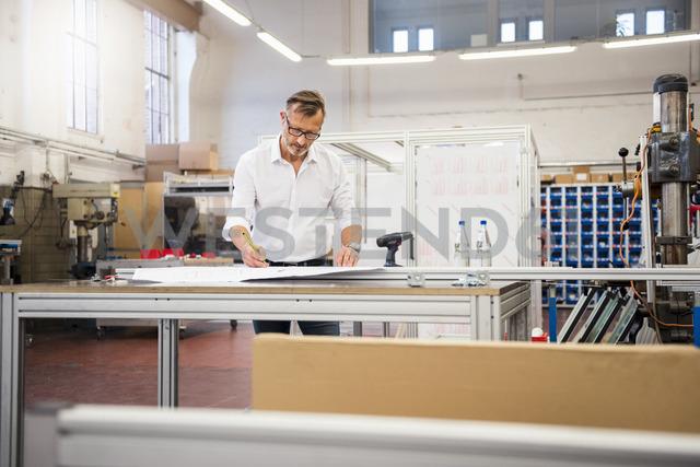 Mature businessman in factory working on plan - DIGF03358 - Daniel Ingold/Westend61