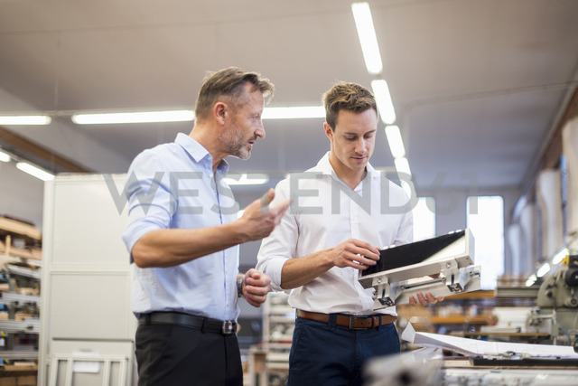 Two businessmen in factory discussing product - DIGF03361