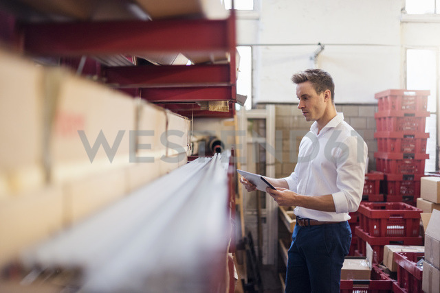 Young businessman in factory storeroom using tablet - DIGF03370