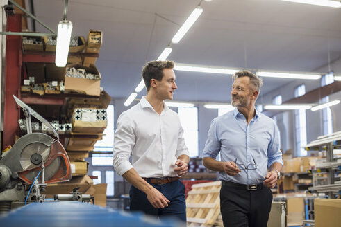Two businessmen walking and talking in factory storeroom - DIGF03376