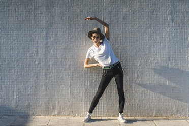 Smiling woman wearing hat standing in front of tiled wall doing stretching exercises - AFVF00101