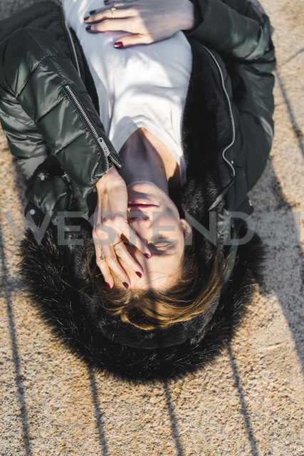 Portrait of woman wearing hooded jacket lying on the ground at sunlight - AFVF00110