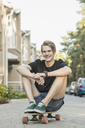 Portrait of smiling young man sitting on skateboard outdoors - FSIF01398