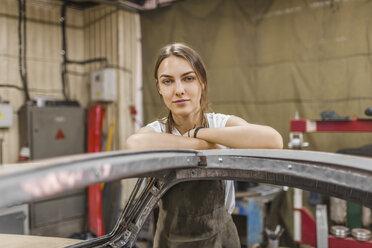Portrait of confident female mechanic leaning on car at garage - FSIF01410