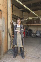 Portrait of confident female mechanic standing arms crossed at garage - FSIF01413