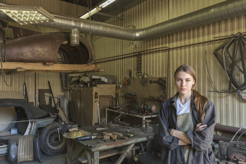 Portrait of confident female mechanic with arms crossed at repair shop - FSIF01416