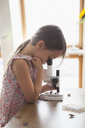 Side view of curious girl looking into microscope on table at home - FSIF01419