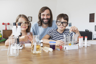 Portrait of father and children doing science experiment at home - FSIF01425