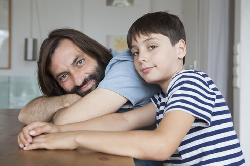 Portrait of father and son sitting at table in house - FSIF01437