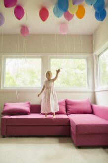 Girl reaching for balloons while standing on sofa at home - FSIF01464