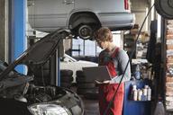 Mechanic using laptop while examining car engine at garage - FSIF01473