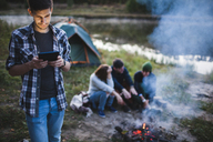 Young man using digital tablet while friends sitting by bonfire in forest - FSIF01527