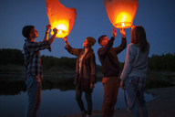 Male and female hikers releasing paper lanterns at lakeshore - FSIF01530