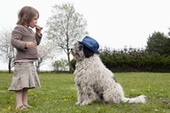 Full length side view of girl eating in front of dog on field - FSIF01533