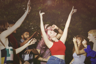 Excited woman dancing with friends at yard during party - FSIF01542