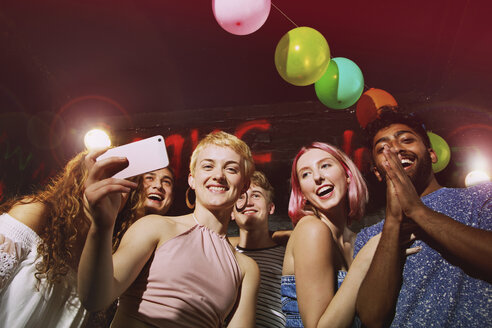 Low angle portrait of happy woman taking selfie with friends at yard - FSIF01563