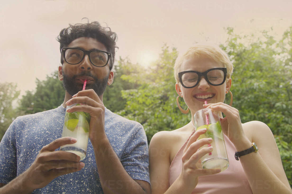 Low angle view of cheerful couple drinking lemonade at yard - FSIF01572 - fStop/Westend61