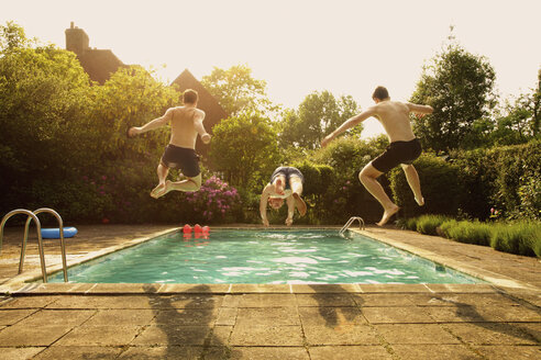 Rear view of men jumping in swimming pool during summer - FSIF01575