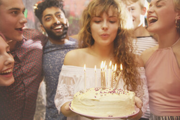Woman blowing candles while celebrating birthday with friends - FSIF01578