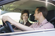 Smiling couple looking at each other while traveling in car - FSIF01584