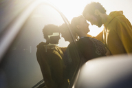 Side view of romantic couple leaning on car - FSIF01593